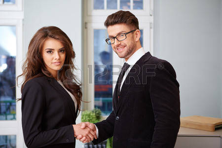 36080059-businessman-and-businesswoman-shaking-hands-in-modern-office